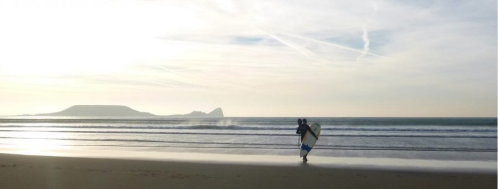 A lone paddleboarder at Rhossili beach